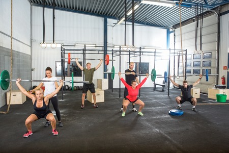 coach sport: Trainers Assisting Athletes In Exercising With Barbells Stock Photo
