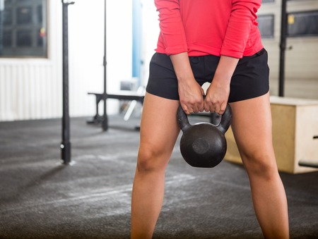 heavy lifting: Woman Exercising With Kettlebell In Gym Stock Photo