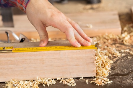 Carpenters Hand Measuring Wood With Scale photo