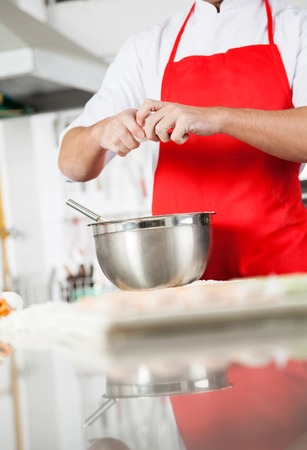 midsection: Midsection Of Chef Breaking Egg In Mixing Bowl At Counter Stock Photo