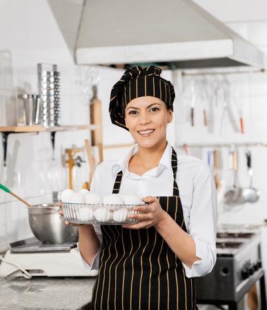 Gelukkig chef-kok Holding Container vol eieren in Keuken