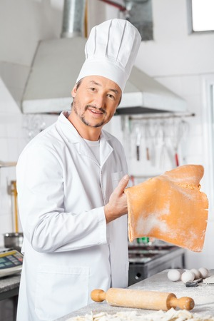 Confident Chef Holding Ravioli Pasta Sheet In Kitchen Stock Photo