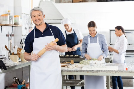 Confident Male Chef Holding Rolling Pin While Colleagues Prepari photo