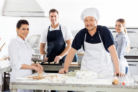 toque blanche: Confident Chefs Preparing Pasta At Kitchen