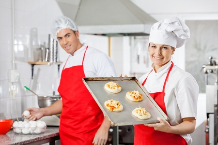 baking tray: Smiling Chef Holding Pizzas On Tray With Colleague In Background