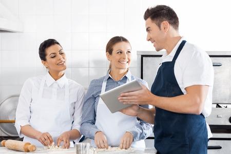 cocinas industriales: Felices Chefs Discutir receta En Tableta digital en cocina