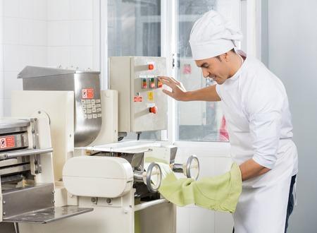 toque blanche: Smiling Chef Operating Spaghetti Pasta Machine