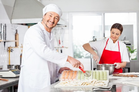 toque blanche: Chefs Preparing Ravioli Pasta In Kitchen Stock Photo