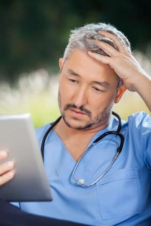 Tensed Male Caretaker Using Tablet PC photo