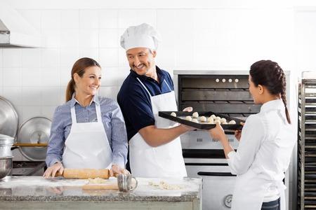 toque blanche: Happy Chefs Baking In Kitchen