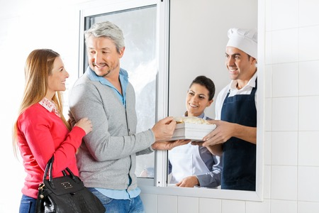 through window: Chefs Selling Pasta Packets To Couple Through Window Stock Photo