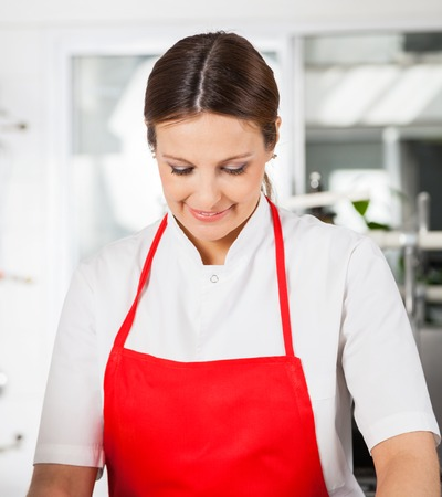 toque blanche: Smiling Female Chef In Red Apron At Kitchen Stock Photo