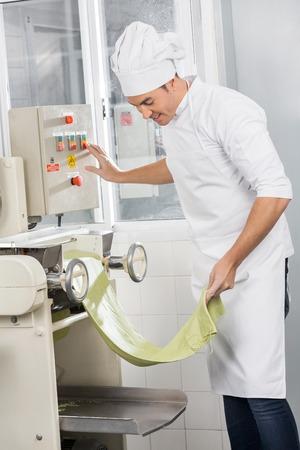 toque blanche: Chef Operating Spaghetti Pasta Machine Stock Photo