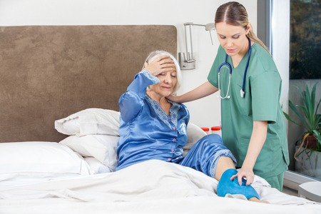 cramp: Caretaker Using Hot Water Bag On Senior Woman