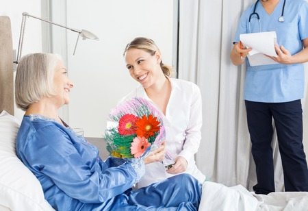 nursing mother: Daughter Giving Bouquet To Sick Mother At Nursing Home Stock Photo