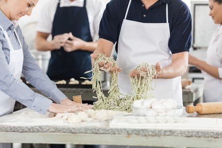 midsection: Midsection Of Chefs Preparing Pasta In Kitchen