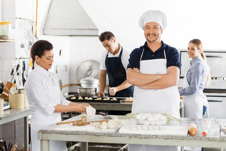 toque blanche: Confident Chef Standing Arms Crossed While Colleagues Preparing Stock Photo