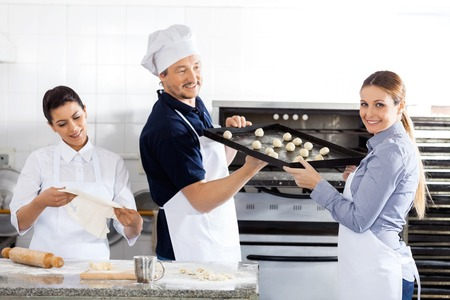 toque blanche: Smiling Chef Passing Baking Sheet To Colleague In Kitchen