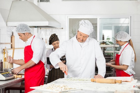 toque blanche: Chefs Cooking Pasta Together In Kitchen Stock Photo