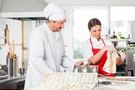 toque blanche: Chefs Cooking Ravioli Pasta In Kitchen Stock Photo