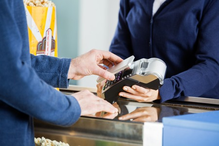 pay bill: Man Using NFC Technology At Concession Counter