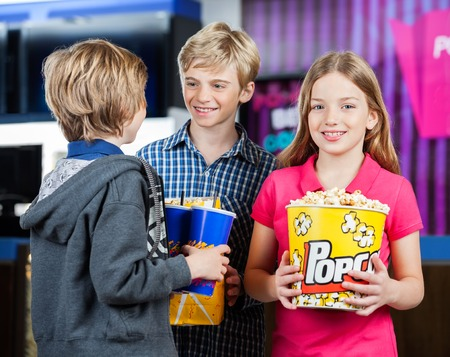 girl bonding: Girl Holding Popcorn While Brothers Talking At Cinema