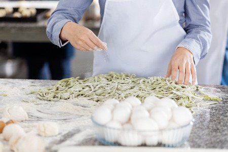 commercial kitchen: Chef Sprinkling Flour On Spaghetti Pasta At Counter In Kitchen Stock Photo