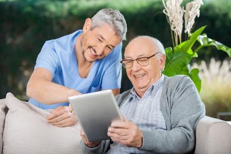 幸せな世話人およびタブレット PC を使用してシニア男性