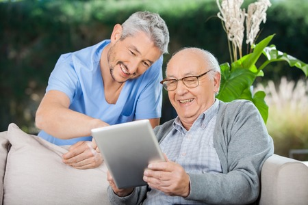 nursing aid: Happy Caretaker And Senior Man Using Tablet PC