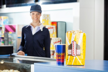 concession: Snacks On Concession Stand At Cinema With Worker In Background Stock Photo