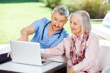Male Caretaker Assisting Senior Woman In Using Laptop Stock Photo