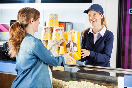 concession: Happy Seller Giving Popcorn To Pregnant Woman At Concession Stan