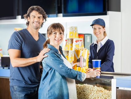 selling service smile: Expectant Couple Buying Snacks From Seller At Cinema Concession