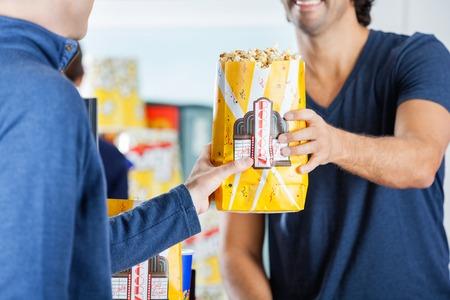 tomando refresco: Vendedor Dar Palomitas Para Hombre En Puesto de comida rápida Foto de archivo