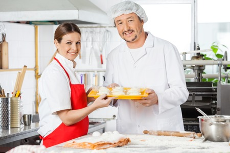 Confident Chefs Holding Pasta Tray In Kitchen photo