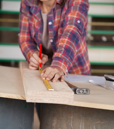 midsection: Midsection Of Carpenter Measuring Wood