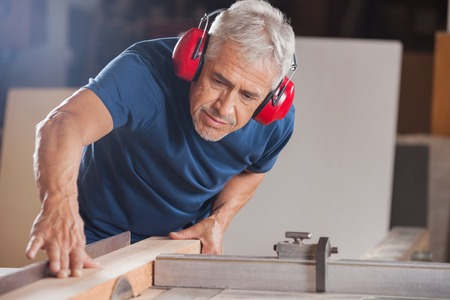 woodworker: Male Carpenter Cutting Wood With Tablesaw