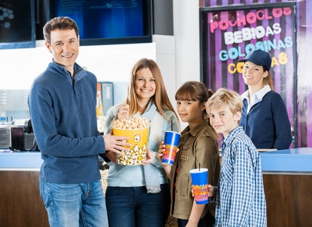concession: Happy Family Holding Snacks At Cinema Concession Stand Stock Photo