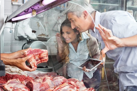 meat counter: Couple Buying Meat At Butchery Stock Photo