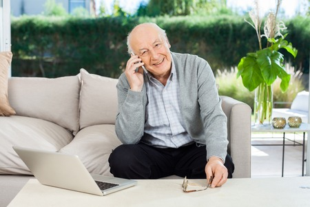 Portrait of smiling senior man answering smartphone while sitting on couch at nursing home porch