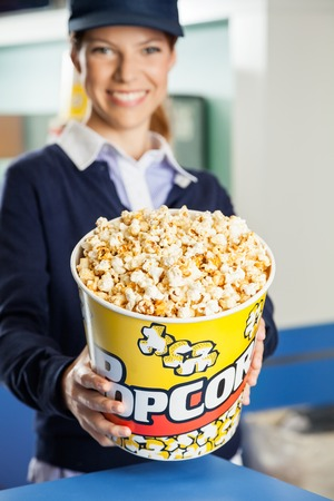 concession: Happy Worker Offering Popcorn At Cinema Concession Stand Stock Photo