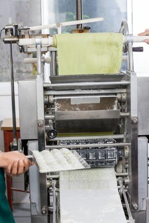 cocinas industriales: Bandeja Pasta Cocinero de sexo femenino Holding Ravioli Por Machine