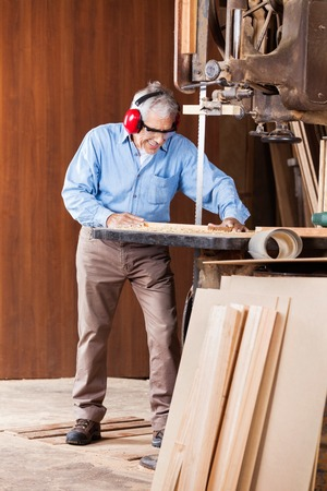 woodworker: Senior Carpenter Cutting Wood With Bandsaw