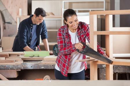 serrucho: Carpintero de cortar madera con serrucho En Taller