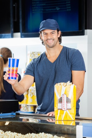 happy worker: Happy Worker Holding Drink At Cinema Concession Stand Stock Photo