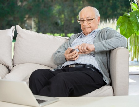 old cell phone: Senior Man Text Messaging Through Smartphone At Porch