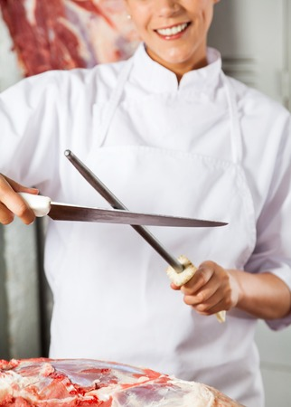 honing: Midsection Of Female Butcher Sharpening Knife