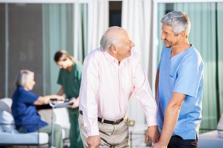 enfermeros: Portero Feliz Con Hombre mayor lisiado en el patio Foto de archivo