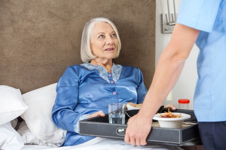 Midsection Of Nurse Serving Breakfast To Senior Woman photo