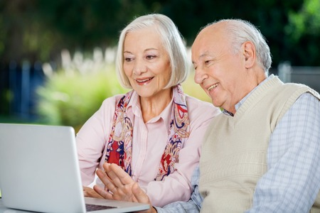 old man happy: Senior Couple Video Chatting On Laptop Stock Photo